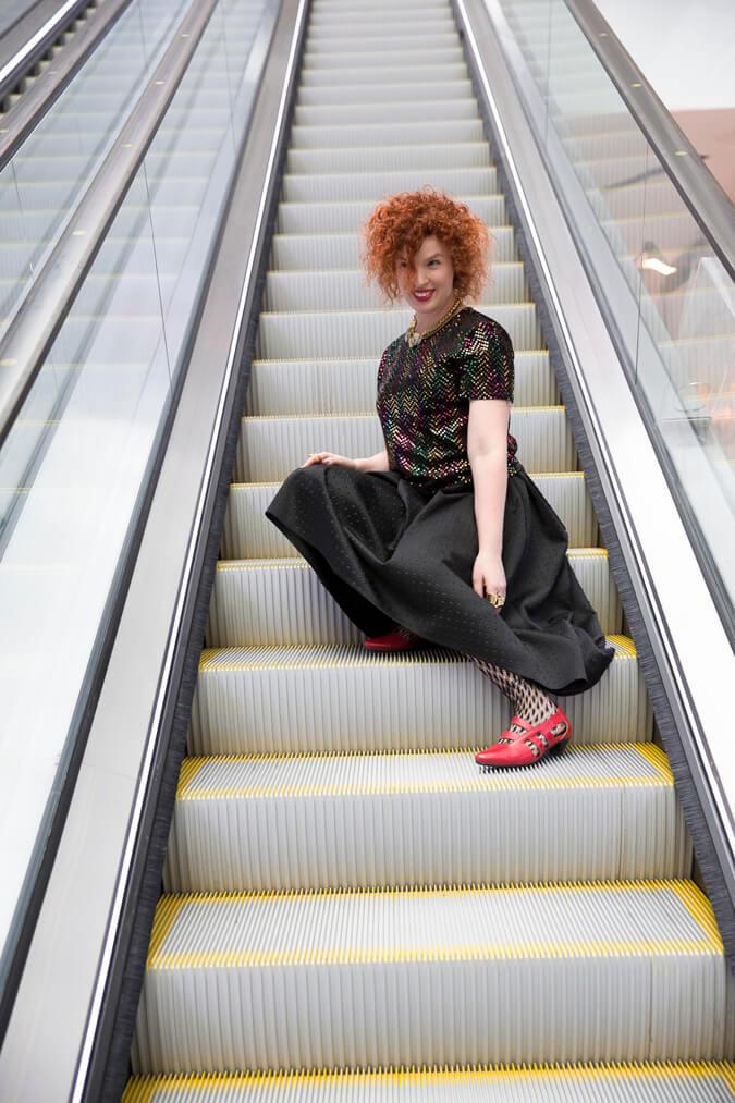 אישה יושבת על מדרגות נעות