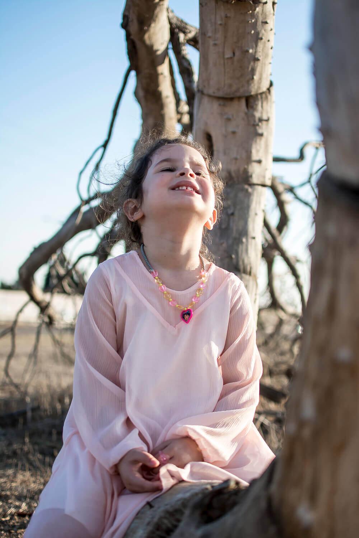 ילדה יושבת על עץ