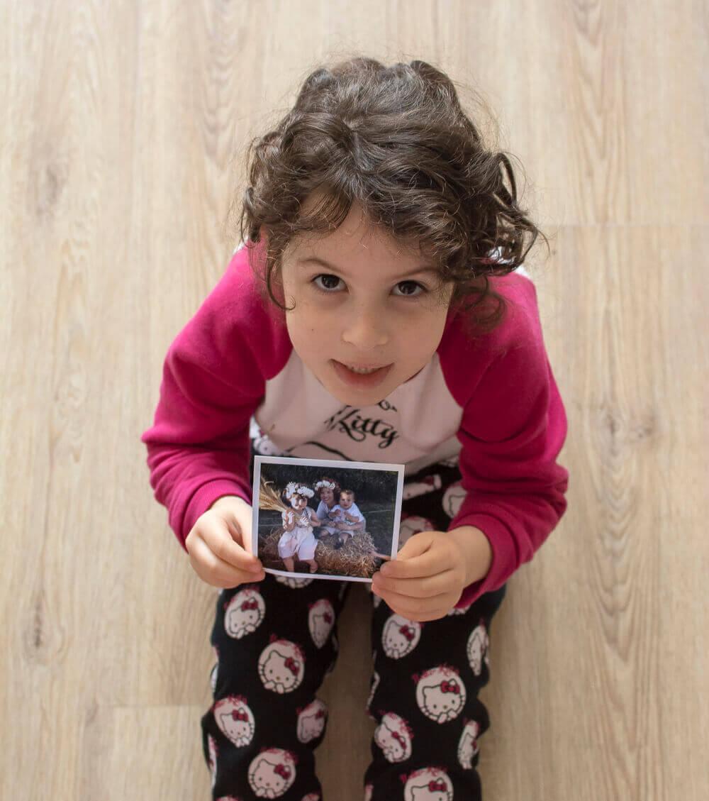 ילדה חמודה מחזיקה תמונה